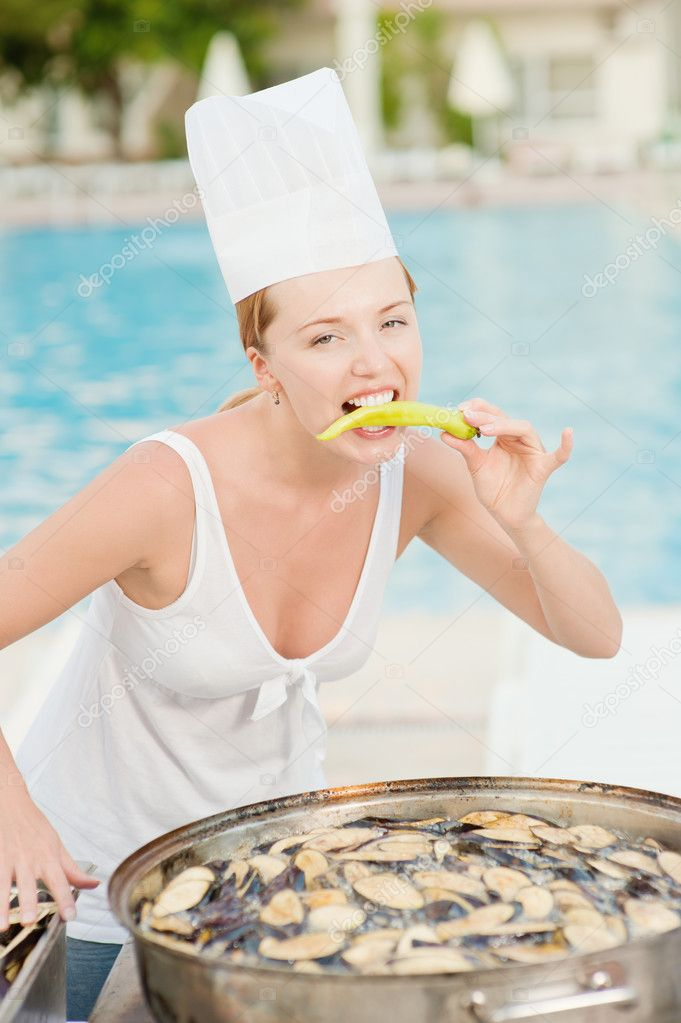 Young beautiful woman-cook tastes food about summer pool on resort. — Stock Photo #5674125