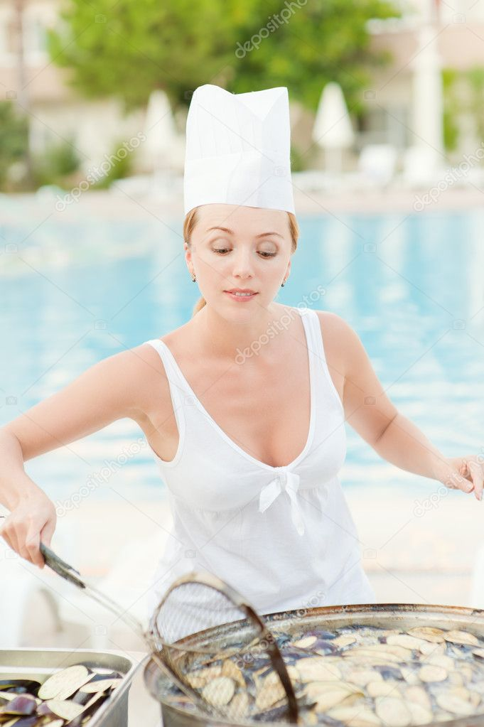 Young beautiful woman cooks food about summer pool on resort. — Stock Photo #5674130