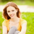 Beautiful girl sits on lawn — Stock Photo #5681749