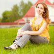 Beautiful girl sits on lawn — Stock Photo