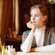 Young beautiful woman sits in cafe - Foto Stock