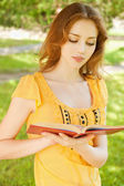 Long-haired girl reads book — Stock Photo