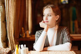 Young beautiful woman sits in cafe — Stock Photo