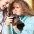 Two girls look through pictures on camera — Stockfoto