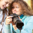 Two girls look through pictures on camera — Stock Photo