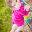 Little girl climbs on horizontal bar - Stock Photo