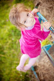 Little girl climbs on horizontal bar — Stock Photo