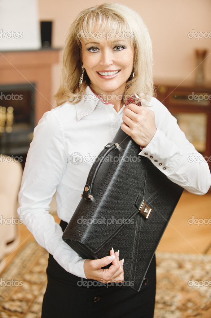 Portrait of beautiful smiling mature business woman in white shirt with black portfolio in hands, against magnificent interior. — Stock Photo #5771893