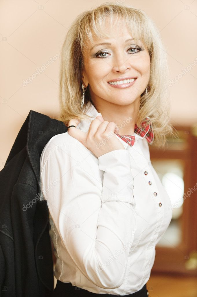 Portrait of beautiful smiling mature business woman in white shirt with jacket , against magnificent interior. — Stok fotoğraf #5771915