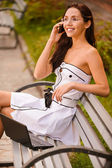 Young woman on bench talks by phone — Stock Photo