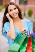 Young smiling woman to purchases and telephone. — Stock Photo