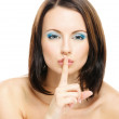 Woman puts forefinger to lips as a sign of silence — Stock Photo #5856097