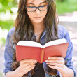 Serious girl reads red book — Stock Photo #5858441