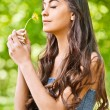 Dark-haired woman smells dandelion - Stockfoto