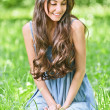 Smiling woman sits on green grass - Stockfoto