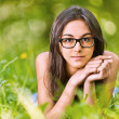 Woman lies on green grass - Stockfoto