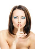 Woman puts forefinger to lips as a sign of silence — Stock Photo