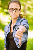 Woman lowers thumb downwards — Stock Photo
