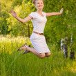 Woman jumps upwards and laughs - Photo