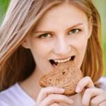 Woman bites piece of bread — Stock Photo