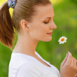 Woman holds small camomile — Stock Photo #5909571
