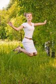 Woman jumps upwards and laughs — Stock Photo