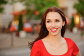 Woman in red dress against city vespers — Stock Photo