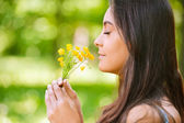 Woman smells yellow florets — Photo