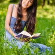 Portrait of beautiful young long-haired woman with book - Stock Photo