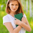 Portrait of beautiful young blond woman with book — Stock Photo