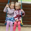 Two girls swinging on playground - Foto Stock