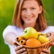 Portrait of woman holding basket with fruits — Stock Photo #6036316