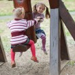 Two little girls swinging - Stock Photo