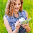 Portrait of young woman counting money - Stock Photo