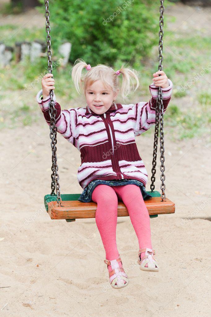 petite fille joyeuse en vtements rouges et roses jouant sur la balanoire image de bestphotostudio