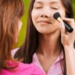 Yong beautiful woman is being made up - Stockfoto