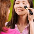 Yong beautiful woman is being made up - Stock Photo