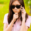 Portrait of woman in sunglasses with phone — Stock Photo
