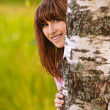 Portrait of laughing girl looking from behind tree - Stock Photo