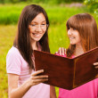Two women read a book — Stockfoto