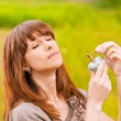 Young woman putting scent on herself - Foto Stock
