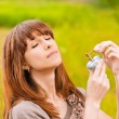 Young woman putting scent on herself - Stock Photo