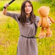 Young angry woman hitting toybear — Stock Photo