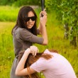 Young beautiful woman hits another with bat — 图库照片 #6056538