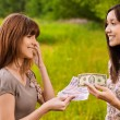 Two young women concluding bargain - Foto Stock