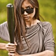 Portrait of young aggressive woman with bat - Stock Photo