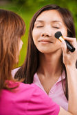 Yong beautiful woman is being made up — Stock Photo