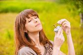 Jeune femme mettant parfum sur elle-même — Photo