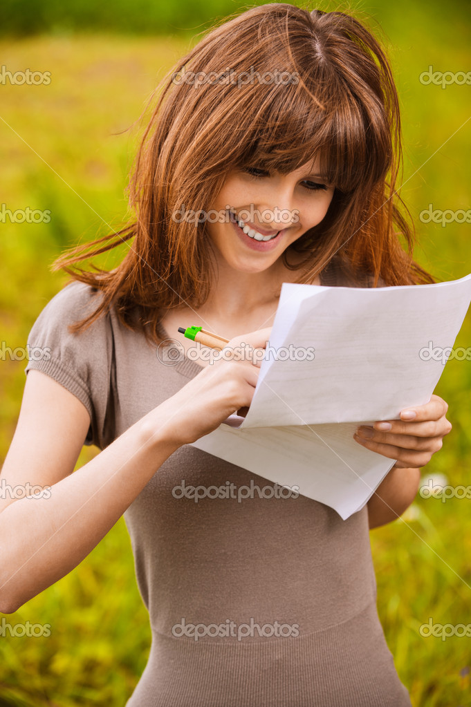 Young happy smiling woman writes something on sheet of paper. — Stok fotoğraf #6056528