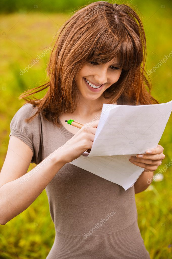 Young happy smiling woman writes something on sheet of paper. — Lizenzfreies Foto #6056528
